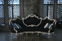 expensive black with silver retro sofa on the background of Windows with daylight in a large dark room with wooden floor