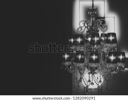Expensive chic chandelier on black background. Chandelier with warm glowing in dark interior, defocused. Chandelier with many lamps and intimate atmosphere. Lighting and mysterious atmosphere concept.