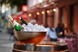 Expensive chilled champagne bottles in a metal bowl on ice standing on wine wooden barrel on the city street to attract visitors to the restaurant. Concept of Social and Cultural Aspects of Drinking.