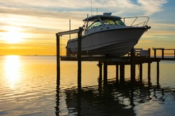 Expensive fishing boat on electric motorized dock vessel lift during sunrise with colorful sky.