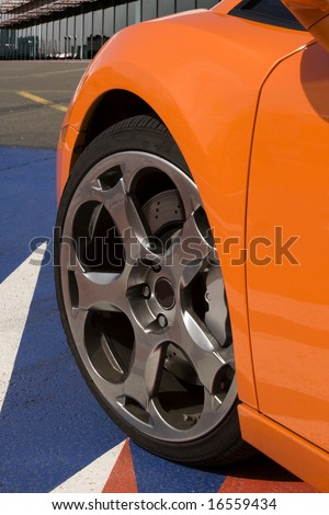 expensive orange super car front tire with office in background
