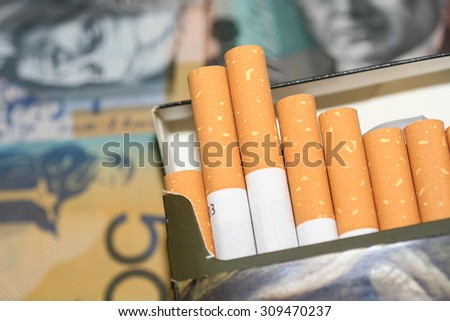 Expensive packet of open cigarettes in front of Australian money.