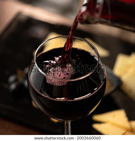 Expensive Red wine pouring into wine glass. Wineglass with merlot or sauvignon on Blurred background. Close up shot. Luxury Alcoholic drink or beverage. Foto d'archivio ©