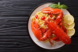 Expensive spaghetti and cooked lobster, tomato, lemon and fresh herbs close-up are served on a plate. horizontal top view from above. Copy space