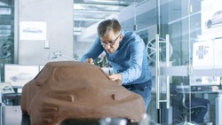 Experience Automotive Designer with a Rake Sculpts Prototype Car Model from Plasticine Clay. He Works in a Modern Studio in a Major Automotive Company's Headquarters.