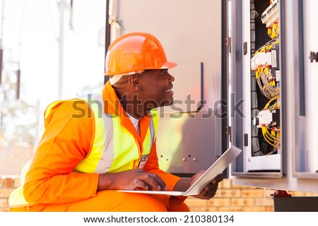 experienced african electrician checking computerized machine status with laptop