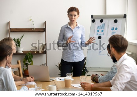 Experienced ambitious businesswoman gives presentation at team meeting standing by flipchart. Excited business coach talking to diverse audience about corporate strategy, financial success, statistics