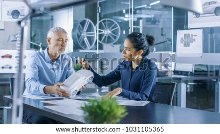Experienced Automotive Designer and Female Engineer Works with a Concept Car Model Prototype, Perfecting it and Making Design Corrections. They Work in a Stylish, Bright, Modern Office.