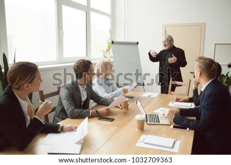Experienced business coach giving presentation to executive managers team explaining strategy with flip chart, senior company leader presenting employees new corporate plan at conference room meeting
