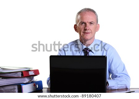 Experienced businessman at his desk with laptop and files.