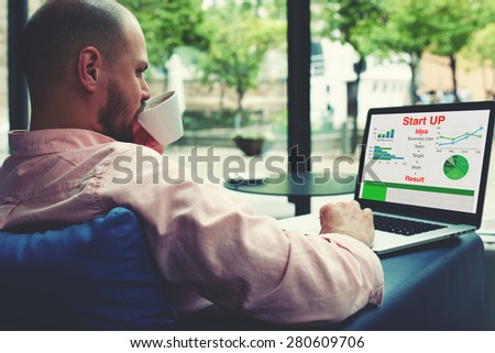 Experienced businessman sitting front laptop computer with financial information as graphics and charts,young entrepreneur work on notebook drinking coffee while sitting in modern hotel interior