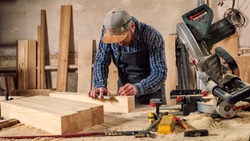 experienced carpenter in work clothes and small buiness owner measures a wooden board with a ruler and marks with pencil the necessary points for slices