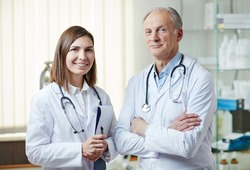 Experienced clinician and his young assistant in whitecoats looking at camera