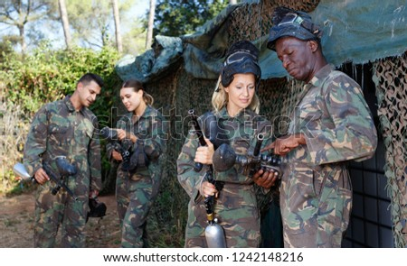 Experienced diligent positive paintball player instructing beginner before game outdoors