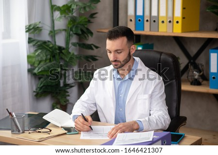 Experienced doctor. Young bearded doctor in a white robe working with papers in his office