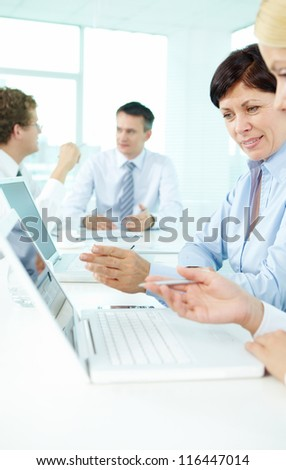 Experienced employee explaining computer terms to her colleague - stock photo