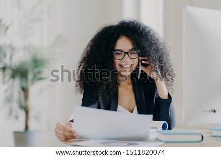 Experienced female CEO has telephone conversation, solves problem, focused in documents, wears spectacles and formal wear, poses at work place, has cheerful expression. Administrative manager