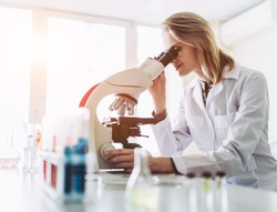 Experienced female scientist is working in laboratory. Doing investigations with microscope.