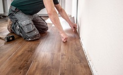 experienced floor layer is laying a new vinyl flooring design