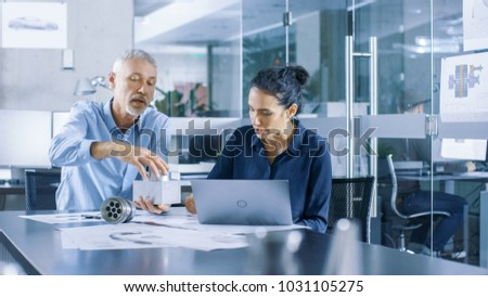 Experienced Male and Female Industrial Engineers have Discussion, Making Adjustment and Perfecting Parts, Type Corrections on a Laptop, They Work on a Machinery Component Design. #1031105275