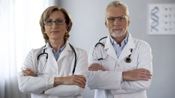 Experienced man and woman doctors looking at camera, arms crossed, guarantee