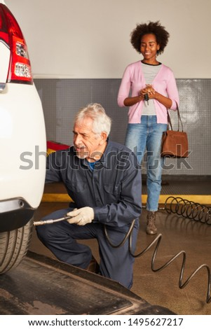 Experienced mechanic checks tire pressure when changing wheels with attentive customer #1495627217