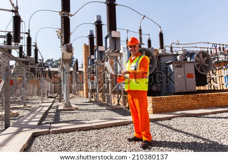 experienced middle aged electrical technician using laptop computer