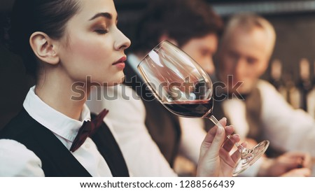 Experienced sommelier woman explores taste of wine in restaurant. Wine tasting. Checking taste, color, sediments of wine Stock photo ©