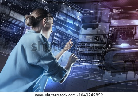Experienced specialist. Enthusiastic reliable programmer smiling and feeling confident while carefully touching the screen of a wonderful futuristic device #1049249852