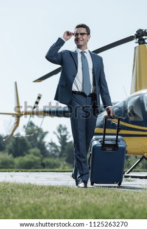Experienced traveler. Upbeat young CEO smiling and adjusting his glasses having arrived after a helicopter flight and carrying a suitcase
