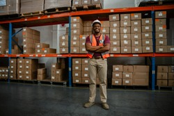 Experienced worker standing proudly in front of packaged parcels with crossed arms in factory