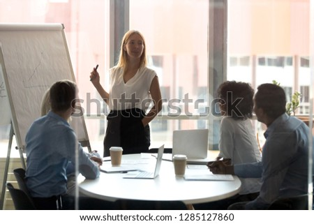Experienced young business trainer speaks to the company members, confident team leader teach interns with nuances of the market provide important information to colleagues while sitting at boardroom
