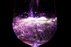 Experimental long exposure photography of water being poured into wine glass dark background purple