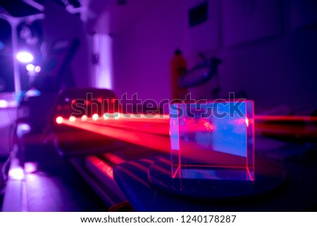 Experiments with lasers in the optics lab. Red laser on optical table in physics laboratory