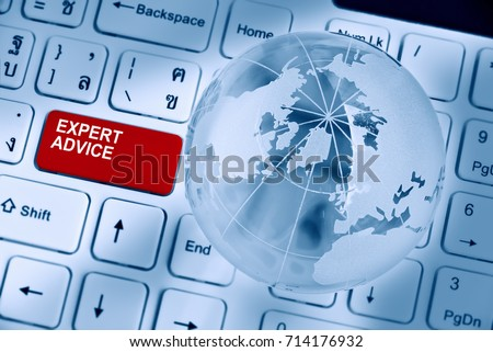 Expert advice and support service concept : Two words EXPERT ADVICE inscribed on a red enter key button of a white desktop computer keyboard decorated with a crystal clear globe and opaque world map.