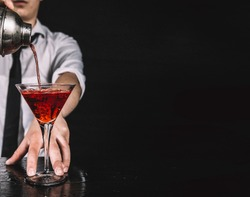Expert barman making cocktail at nightclub.  Bartender preparing red cocktail at cocktail glass at the bar. Preparing of cosmopolitan cocktail. Red alcoholic drink in glasses on bar.