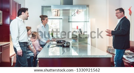 Expert explaining new kitchen to family looking for one pointing at some interesting features of the current model  Foto stock ©