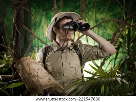 Expert explorer in the jungle looking away through binoculars. #221547880