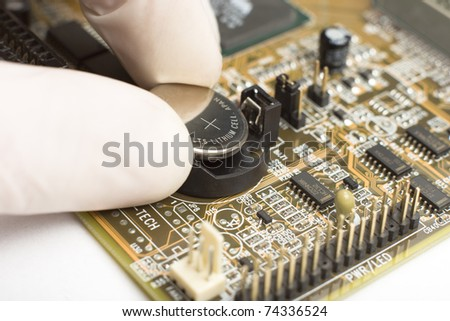 expert in white mitten on hand is putting round reflective battery with plus sign into computer motherboard