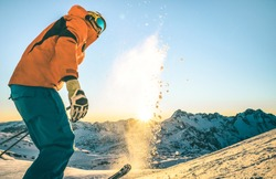 Expert professional skier at sunset on relax moment in french alps ski resort - Winter sport concept with adventure guy on mountain top ready to ride down - Side view point with teal and orange filter