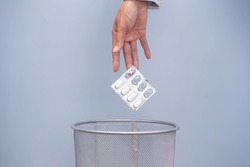 Expired medicine. Woman's hand throws expired medicine in the trash. improper disposal of the drug Medicines should not be placed in trash or water sources.