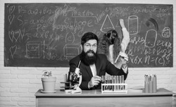 Explaining biology to children. Man bearded teacher work with microscope and test tubes in biology classroom. Biology plays role in understanding of complex forms of life. School teacher of biology.