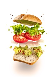 Exploded and flying vegetarian sandwich with guacamole and tofu cheese on white