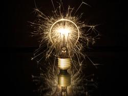 exploding lightbulb in front of black background