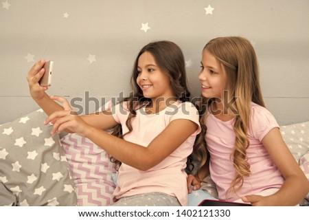 Explore social network. Smartphone for entertainment. Kids taking selfie. Smartphone application concept. Online entertainment. Girlish leisure pajama party. Girls smartphone little bloggers.