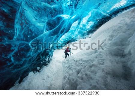 Explorer inside ice cave at Vatnajokull glacier, Iceland