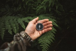 Explorer people holding a compass and searching the right directions in the jungle.Survival travel,lifestyle concept.