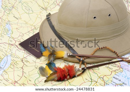 Explorer's hat and passport over map - stock photo