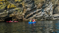 Exploring cliffs and sea caves on the coast between Latheronwheel and Lybster in Caithness in the Highlands by canoe and kayak
