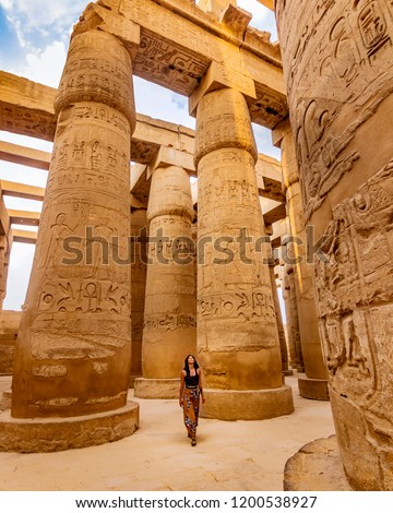 EXPLORING EGYPT - Young female traveller wandering through ancient Karnak Temple. Beautiful Egyptian landmark with hieroglyphics. Travelling woman adventuring around the world. Luxor, Egypt